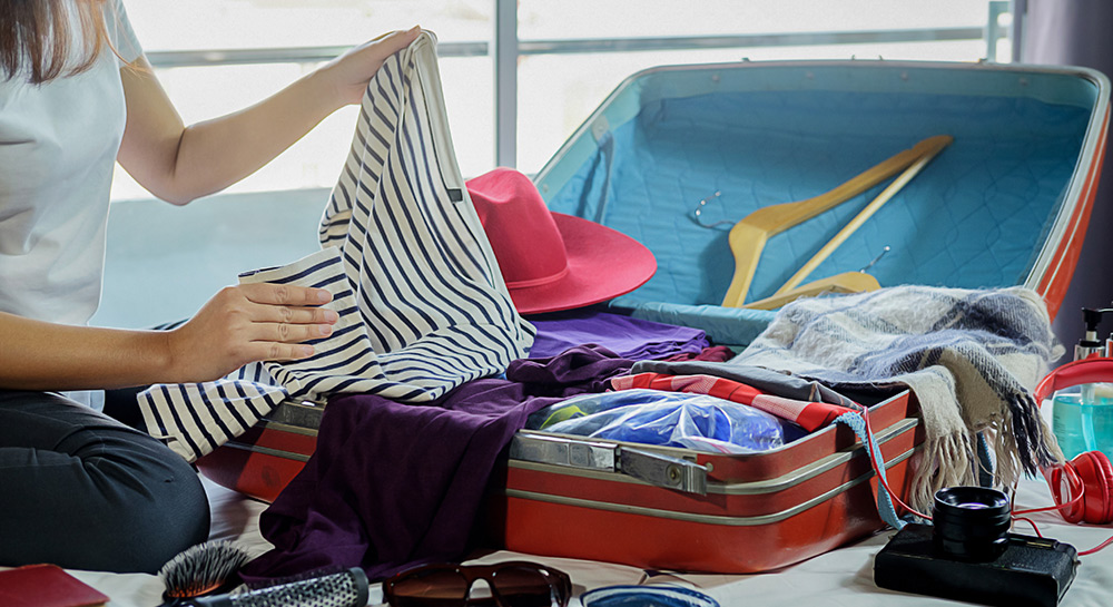 Woman packing suitcase for zero waste travel